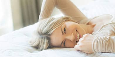 woman laying on a bed smiling